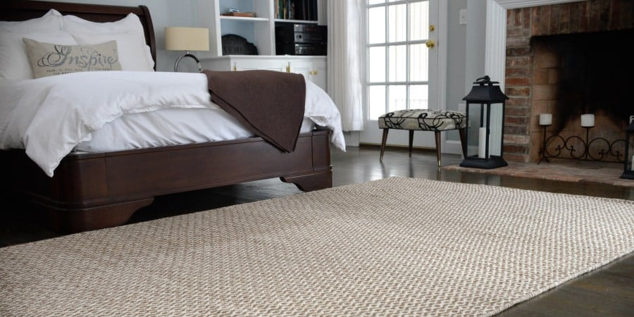 A lovely Merino Natural Undyed Woven Wool rug sits by bed and fireplace