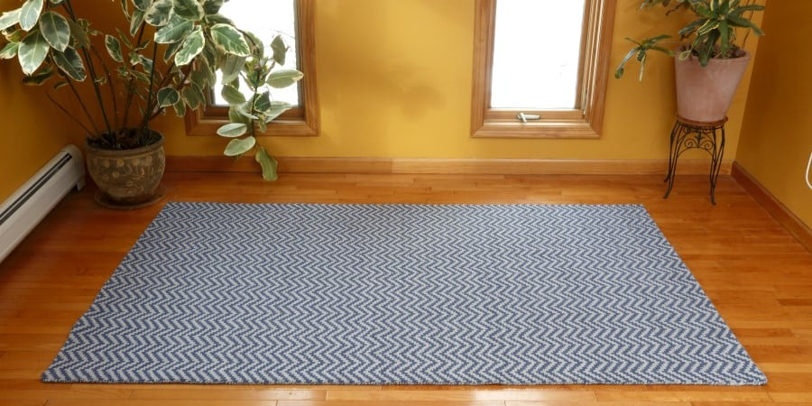 New Waves Blue/Grey Eco Cotton Loom-Hooked Rug in a warm yellow room with houseplants