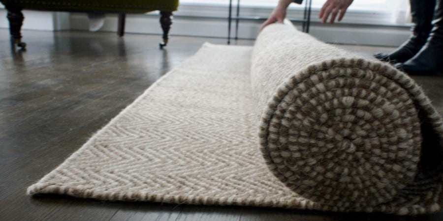 Unrolling a Suffock Natural Undyed Woven Wool rug!