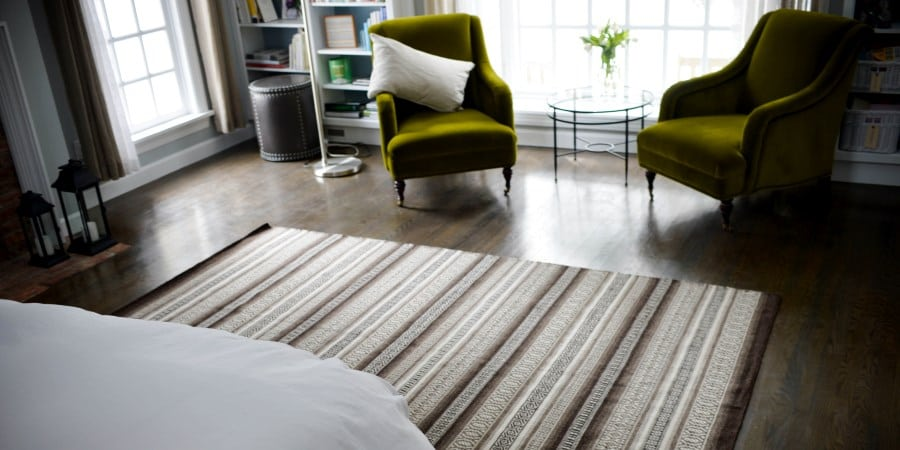 Tunis Natural Undyed Wool Flatweave rug framed by green chairs and a bed